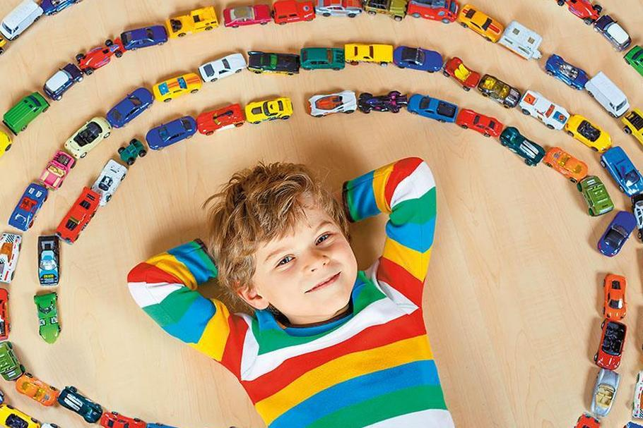 Cute little blond kid boy playing with lots toy cars