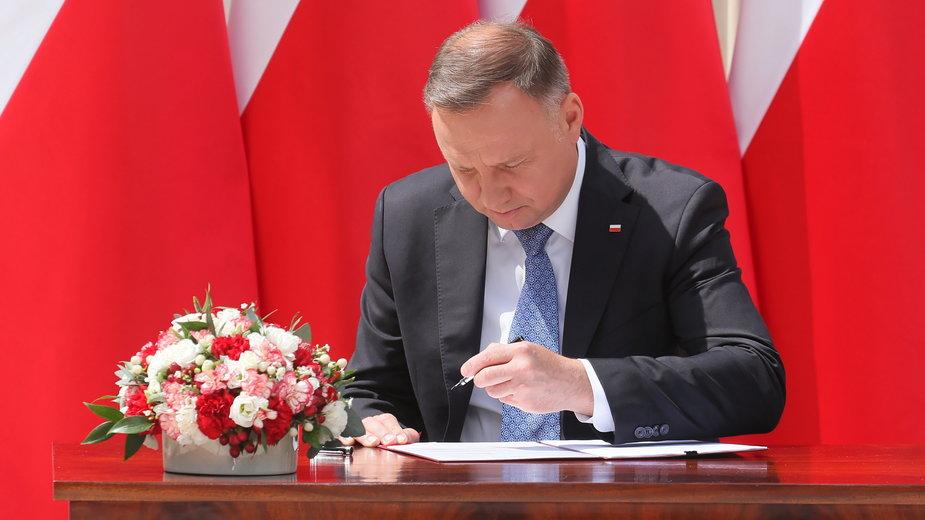 Andrzej Duda podpisujący projekt zmian w Konstytucji