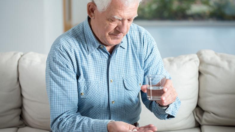 Starszy mężczyzna przyjmujący lekarstwa