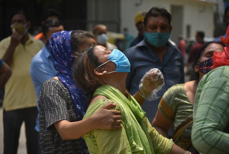 Indiai család gyászolja koronavírusban elhunyt rokonát Új-Delhiben, egy halottasház előtt / EPA/IDREES MOHAMMED