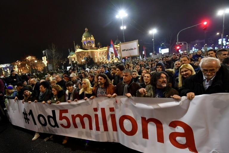 "Thousands of people, many blowing whistles, hold a banner that reads, ""One out of five million"", as they protested against the Serbian president in Belgrade last month"