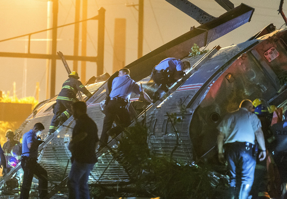 Rescue workers climb into the wreckage of a derailed Amtrak train to search for victims in Philadelphia