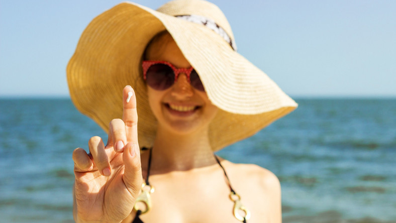 Kobieta w kapeluszu ma na palcu krem przeciwsłoneczny
