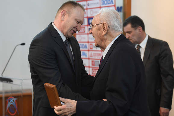 Bora Stanković uručuje Draganu Đilasu Zlatnu značku KSS-a