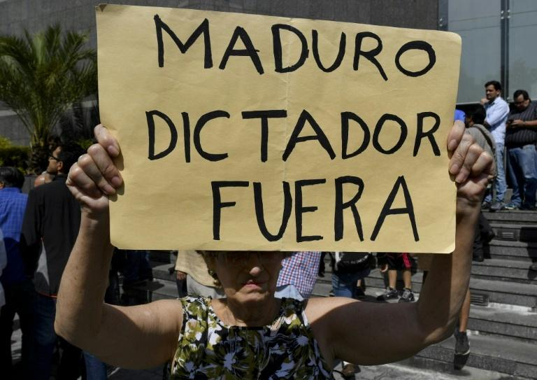 "The sign held by an anti-government activist at the rally where Juan Guaido spoke reads ""Maduro dictator out"""