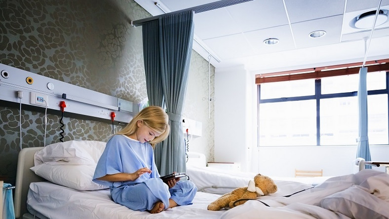 Little girl sitting on a hospital bed playing with a digital tablet