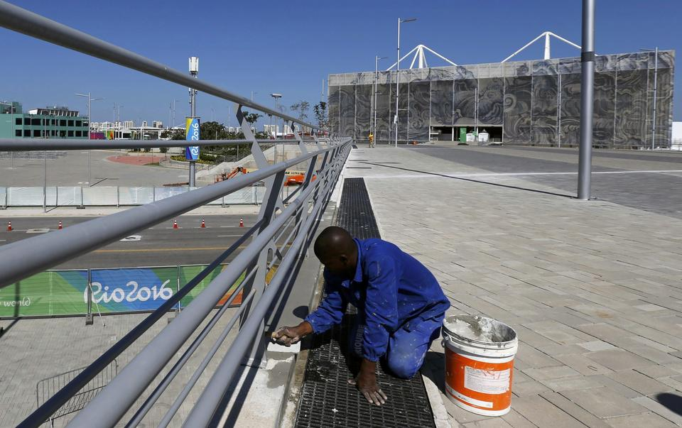A worker applies cement to the base of a railing at the Olympic Park in Rio de Janeiro
