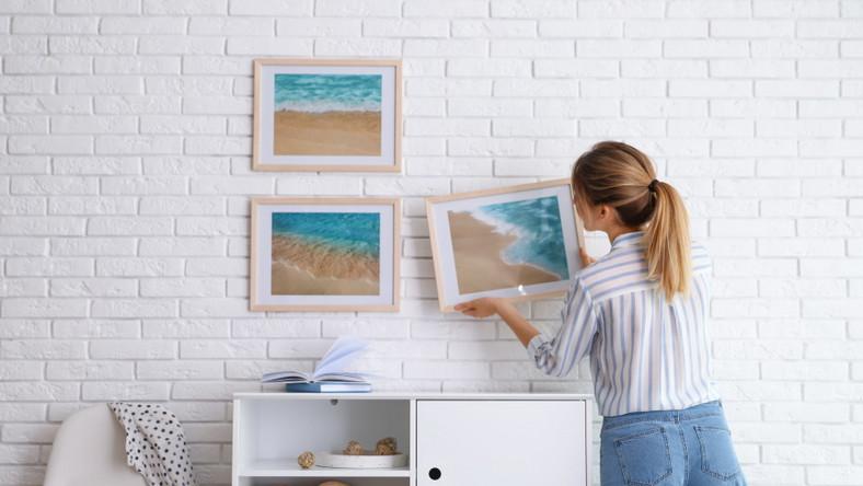 Kobieta wiesza obrazki na ścianie. Dekoracja wnętrz