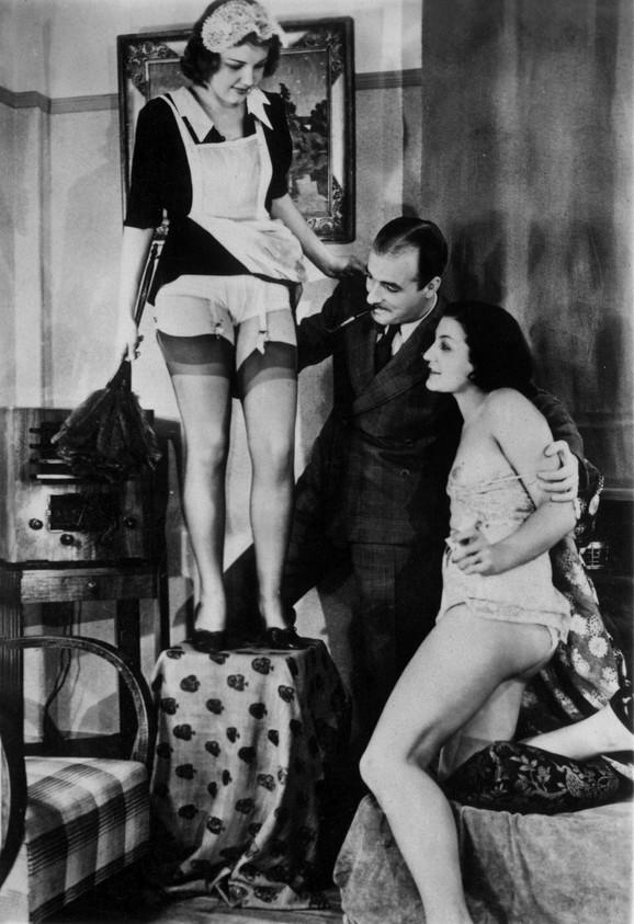 Muškarac sa dve prijateljice noći, od kojih je jedna obučena u odelo sobarice, a druga poluobnažena