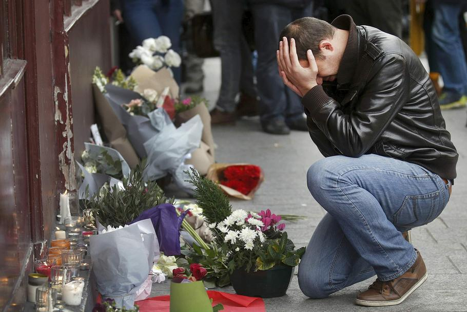 A man pays his respect outside the Le Carillon restaurant the morning after a series of deadly attacks in Paris