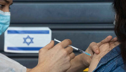 An Israeli receives a coronavirus vaccine from medical staff at a COVID-19 vaccination center in Tel Aviv, Israel, Wednesday, Jan. 6, 2021.