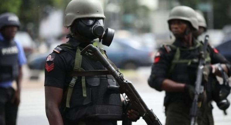 A Nigerian police officer wearing a gas mask