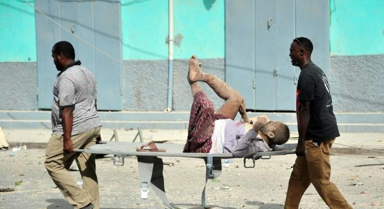 Residents carry an injured man wounded during a complex car bomb attack targeting a Mogadishu hotel on January 25, 2017