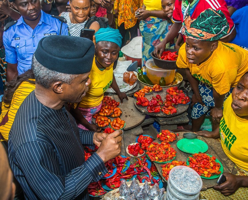Vice-President Yemi Osinbajo sits with beneficiaries of the TraderMoni loan scheme in a market in Ibadan, Oyo State. [Premium Times]