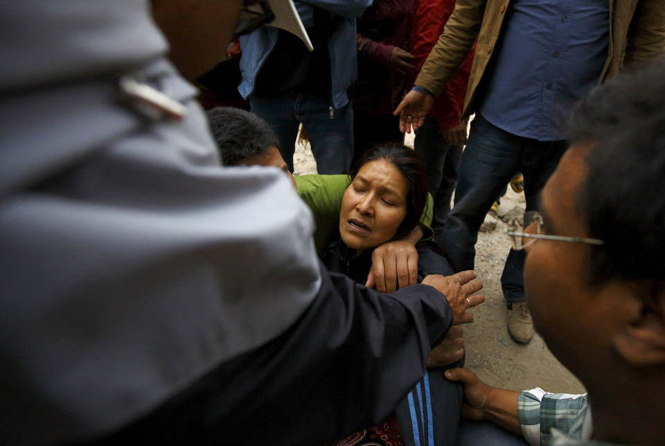 Woman cries as her son was trapped inside a collapsed house after an earthquake hit, in Kathmandu