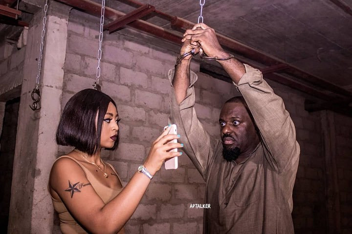 Kenya (played by Regina Daniels) dealing with one of the Merry Men, Naz Okigbo (played by Jim Iyke) on the set of 'Merry Men 2', [Instagram/regina.daniels]