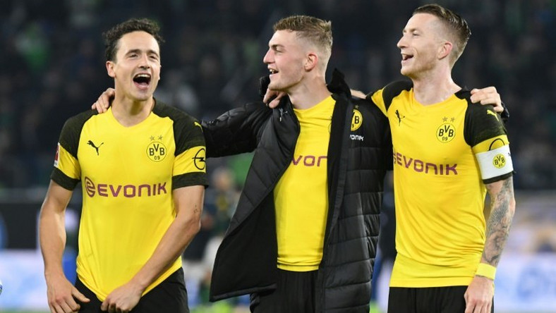 Borussia Dortmund midfielders Thomas Delaney (L), Jacob Bruun Larsen (C) and Marco Reus (R) celebrate Saturday's 1-0 win at Wolfsburg - a new club record of 15 games unbeaten - ahead of Tuesday's tough Champions League game away to Atletico Madrid.