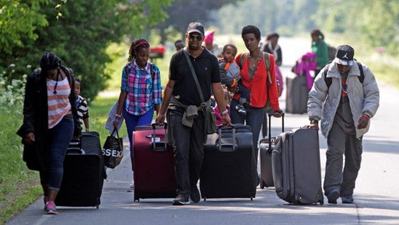 Asylum seekers walk down Roxham Road to cross into Quebec at the U.S.-Canada border in 2017