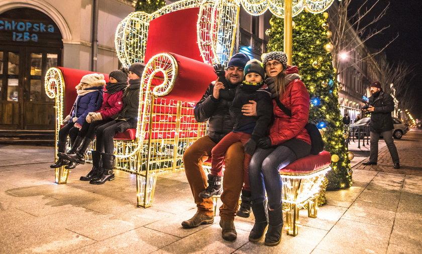 Łódź w świątecznej iluminacji. Ulica Piotrkowska z choinką, gwiazdkami i fotelem świętego Mikołaja