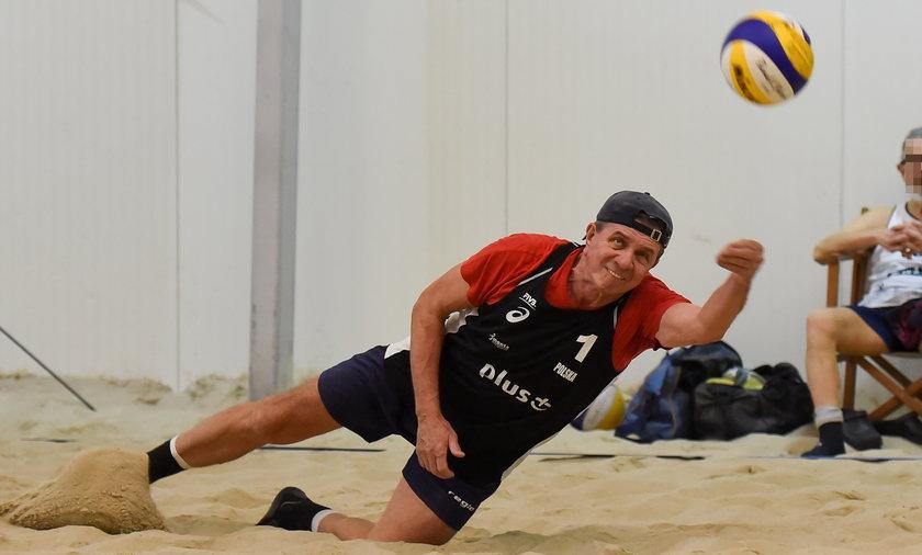 Zygmunt Chajzer gra w siatkówkę plażową na hali.