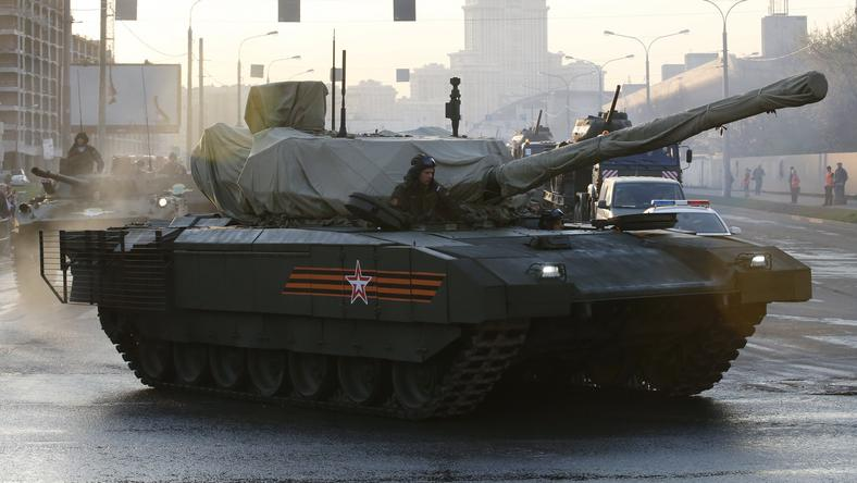 Russian servicemen drive a partially covered T-14 Armata tank along a street before a rehearsal for the Victory Day parade in Moscow