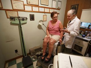 Dr. Bryon Harbolt examines patient Barbara Kilgore in his Cathedral Canyon Clinic in Altamont