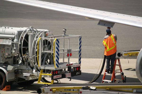 A pump attendant fuels a commercial jet before take off .