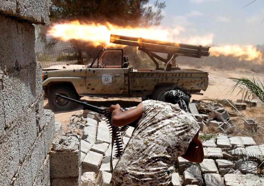 Libyan forces allied with the U.N.-backed government fire weapons during a battle with IS fighters i