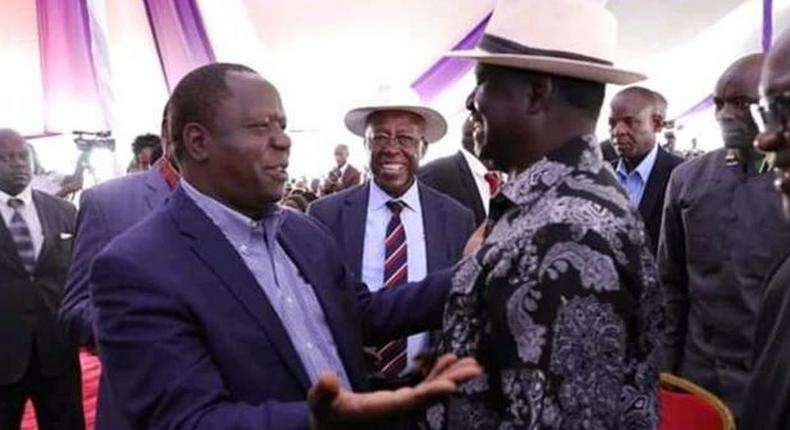Raila Odinga with Fred Matiangi at the burial of Hezron Manduku