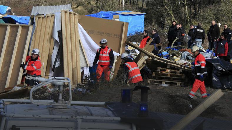 "Workmen tear down makeshift shelters during the partial dismantlement of the camp for migrants called the ""jungle"", in Calais"