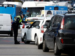 A police traffic officer speaks to motorists entering the center of Madrid