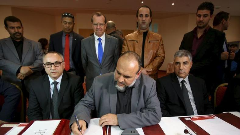 United Nations Special Representative and Head of the U.N. Support Mission in Libya Martin Kobler (C, top) looks on as representatives of Libyan municipalities sign documents to support Libya's new national government during a meeting in Tunis, Tunisia, December 21, 2015. REUTERS/Zoubeir Souissi