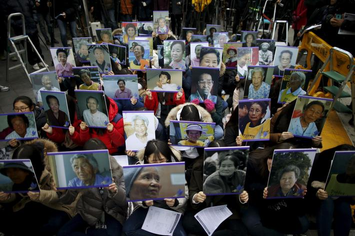 "Students hold portraits of deceased former South Korean ""comfort women"" during a weekly anti-Japan r"