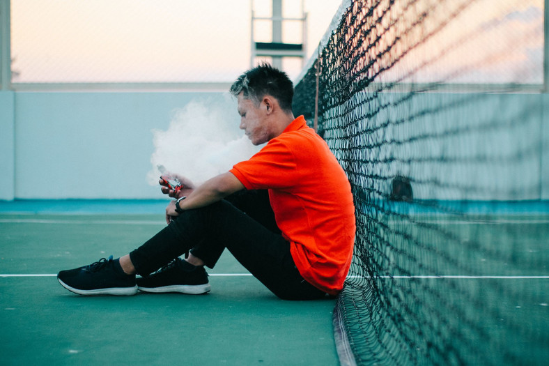 Side View Of Young Man Smoking Electronic Cigarette While Sitting On Tennis Court