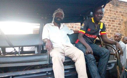 Paul Kiveyiganga, on the left, owner of the scrap shop