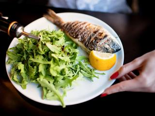 Grilled whole sea bream served with rocket salad and lemon
