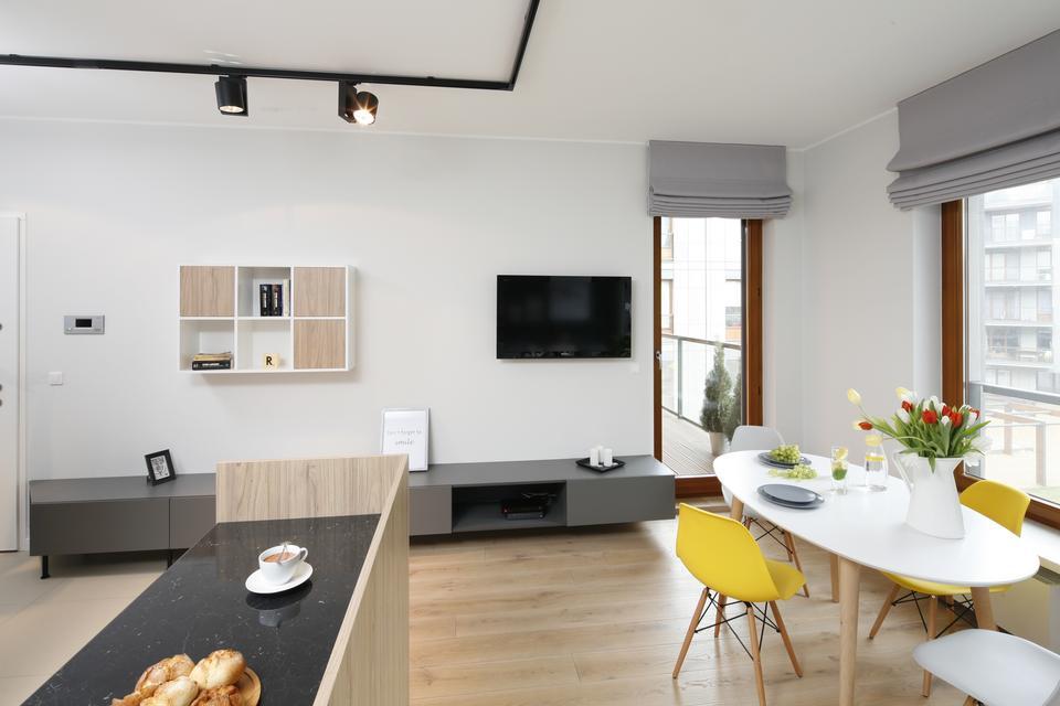 Duże nisko osadzone okna i otwarty plan strefy dziennej sprzyjały urządzeniu wnętrza w estetyce łączącej elementy loft i vintage.