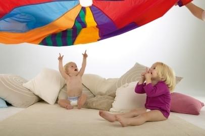 Nawet na siedząco można rozwijać sprawność ruchową u dziecka (np. zabawa w spadochron)