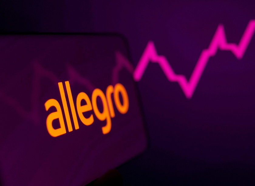 Allegro logo is seen on the smartphone in front of displayed stock graph in this illustration