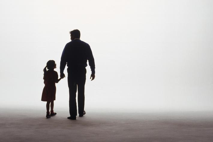 Silhouette of father and daughter walking into fog