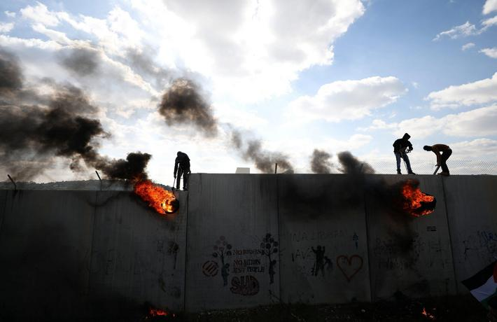 Palestinian protesters lift burning tyres as they climb over a section of the Israeli barrier during