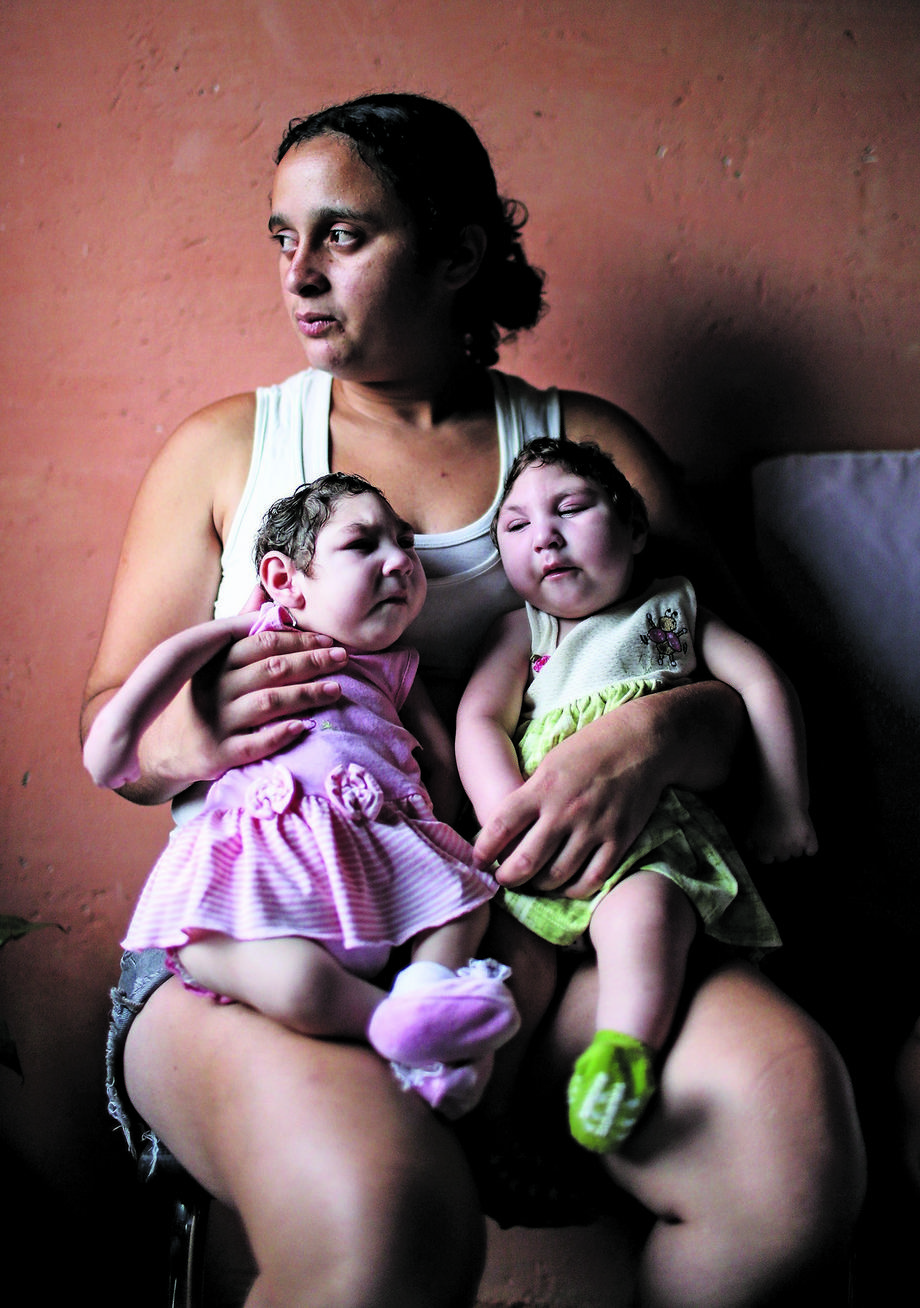Mother Raquel Bholds her twin daughters Eloa (L) and Eloisa, 8 months old and both born with microcephaly, while posing in the home of grandparents of the twins on December 16, 2016 in Areia, Pernambuco state, Brazil.