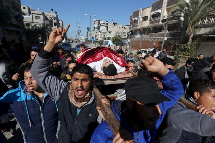Mourners carry the body of Palestinian Qeta, whom a Palestinian medical official said was shot and k