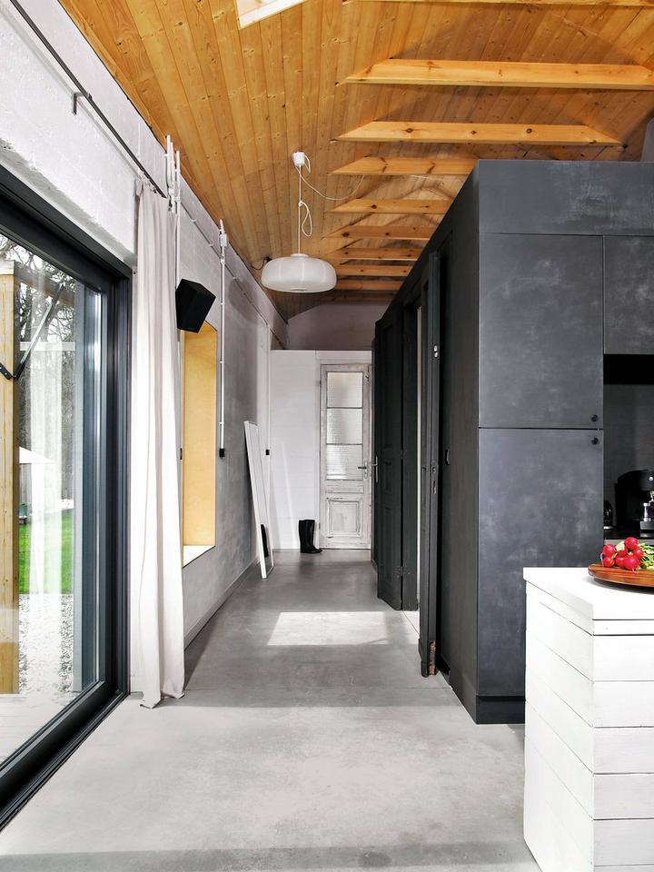 CZARNY KOLOR zabudowy kuchennej oraz ścian wydzielających przedsionek i toaletę efektownie kontrastuje z barwą drewna na suficie.