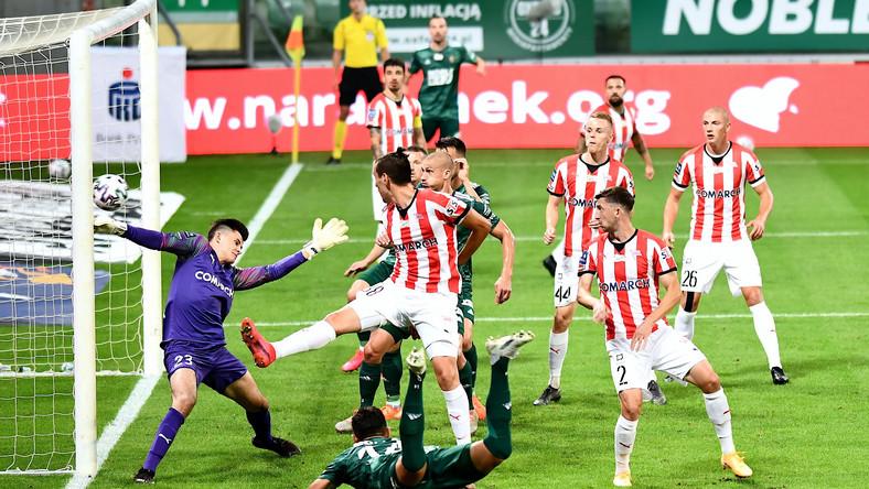 Piłkarz Śląska Wrocław Wojciech Golla (C-przód) pokonuje bramkarza Karola Niemczyckiego (L) z Cracovii podczas meczu Ekstraklasy
