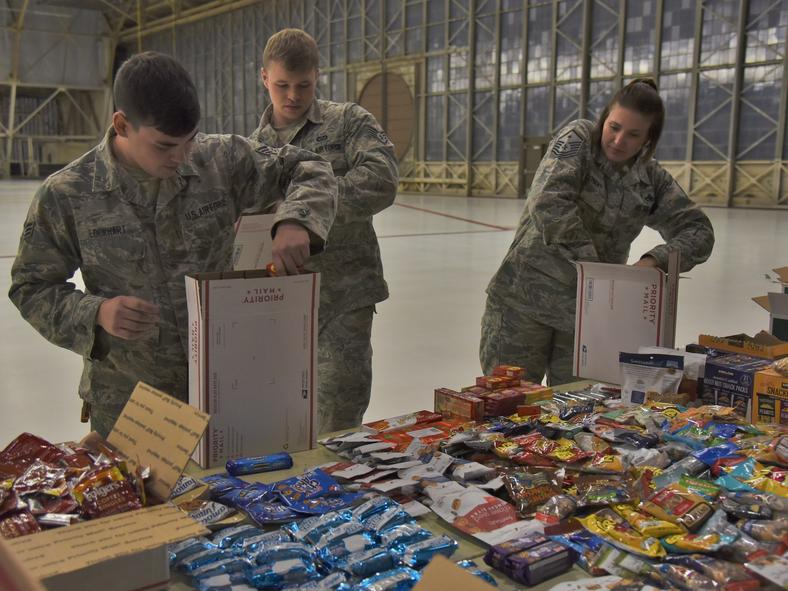 Team Fairchild volunteers pack care packages with donated snacks at Fairchild Air Force Base, Washington. The team pairs with local news organization KREM 2 to send gifts to military members serving overseas.