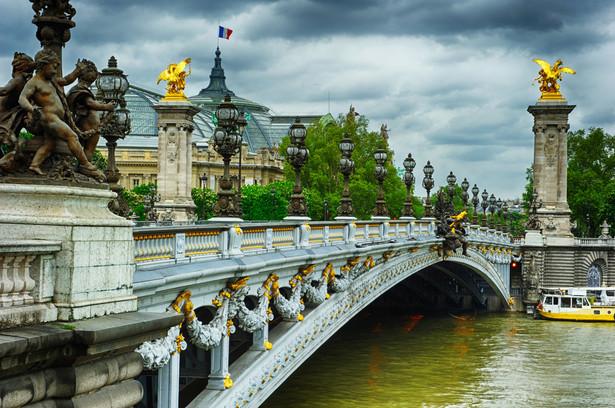Z początkiem października 1896 r. przyjechało do Paryża, żeby powitać cara, 930 tys. Francuzów. Miejsca w oknach na trasie planowanego przejazdu gościa właściciele domów udostępniali za kwotę 200 franków od osoby. Przez dwa dni uprzejmościom okazywanym Mikołajowi II nie było końca. Cara poproszono nawet o wmurowanie kamienia węgielnego pod nowy most na Sekwanie (na zdjęciu), który dla przypochlebienia się sojusznikowi nazwano imieniem Aleksandra III. Prasa prześcigała się w okazywaniu zachwytów Rosji i jej władcy. Tak podejmowani Rosjanie z miejsca pokochali Paryż.