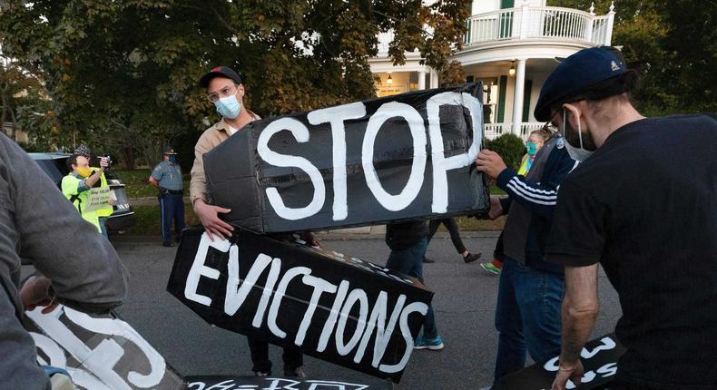 Housing activists erect a sign in front of Massachusetts Gov. Charlie Baker's house in Swampscott, Mass.