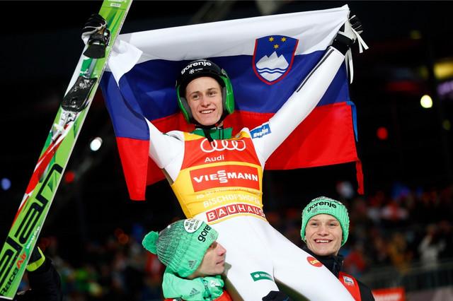 Peter Prevc sa slovenačkom zastavom na ramenima kolega