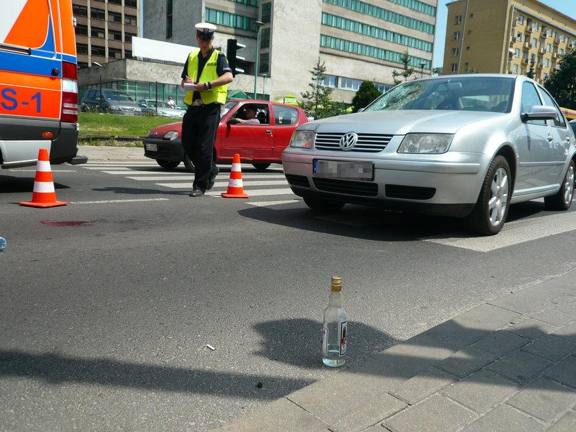 butelka wódki na ulicy i policjant z drogówki